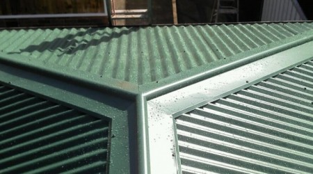 Corrugated garage roof with two hips.